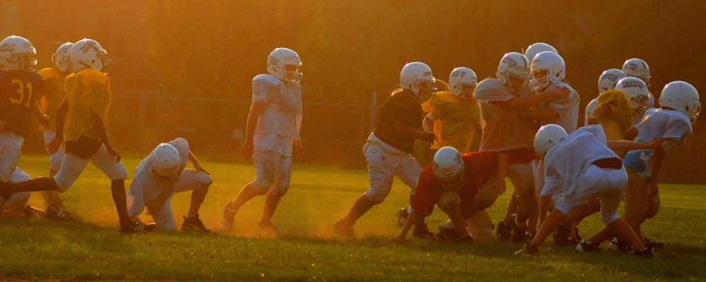 A group of young boys playing football wearing helmets, pads, and jerseys on a green field as the sun sets