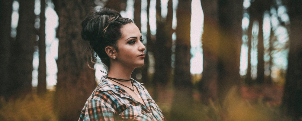 Brunette woman standing in a forest while wearing a plaid shirt looks away anxiously as she thinks about the dentist