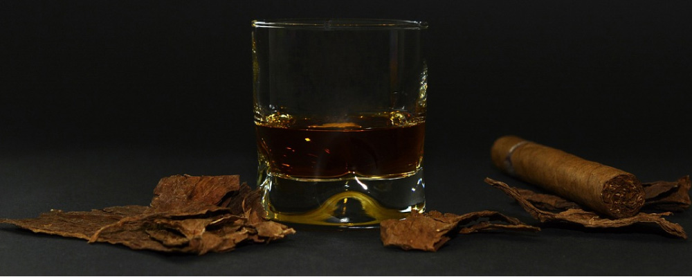 glass of whiskey with cigar, tobacco leaves and oral cancer threat
